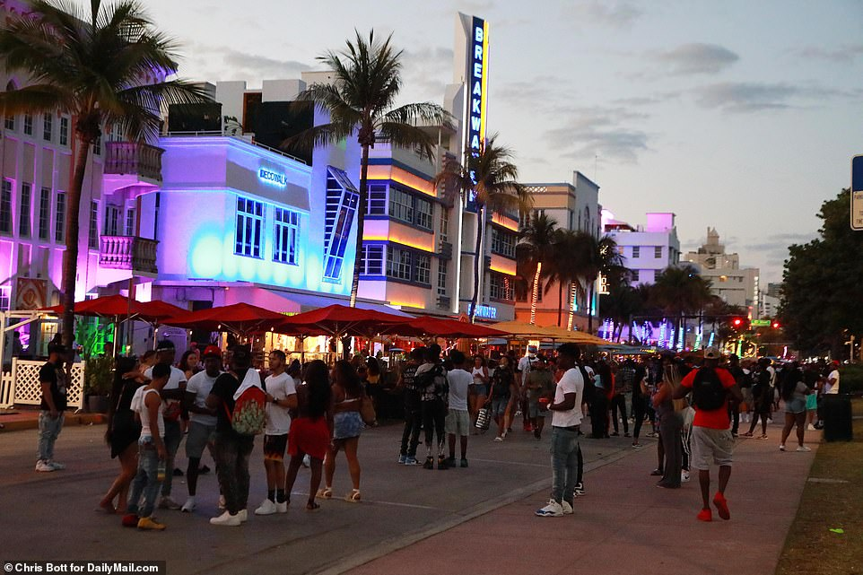 US coronavirus cases could be set to surge again in the Sunshine State and countless Spring Breakers continue to party in the streets despite police patrols and curfews in destinations like South Beach in Miami. Pictured: crowds ignore social distancing guidelines on Ocean Drive in South Beach, Miami on Monday